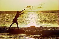 Hawaiian man with throw net fishing at sunset