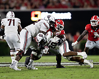 ATHENS, GA - SEPTEMBER 18: Kevin Harris #20 is tackled by Devonte Wyatt #95 during a game between South Carolina Gamecocks and Georgia Bulldogs at Sanford Stadium on September 18, 2021 in Athens, Georgia.