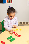 Education preschool 3 year olds girl sorting plastic colored toy pieces by shape and color