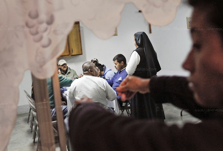 """Mother Ines (at right in background), the Catholic nun who manages the """"Casa Migrante"""", an immigrant shelter in Tecate, Baja California, Mexico, talks to a group of immigrants during dinner at her facility on February 7, 2013.  This immigrant shelter houses and feeds thousands of immigrants every year. With a total capacity of 40 beds, male migrants can stay in the premises for a total of 4 nights before moving on. Places such as Casa Migrante are popular amongst immigrants and deportees making their way back into the United States. (Javier Manzano / For The Washington Post)."""