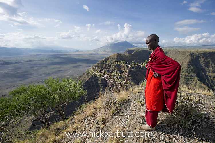 Maasai man overlooking the Great Rift Valley with active volcano Oldonyo Lengai in the background. Ngorongoro Conservation Area, Tanzania.