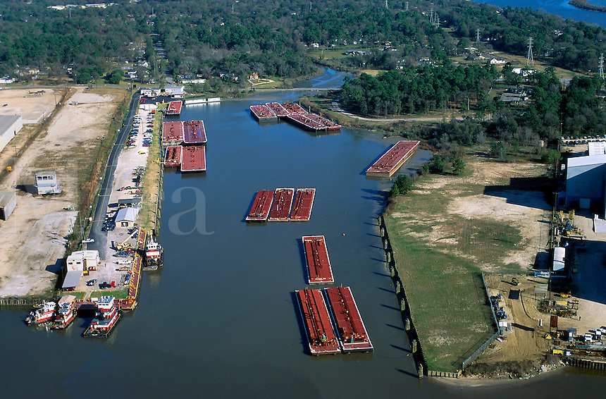 Aerial view of barges moored along the islets and dock on the San Jacinto River upstream from the confluence of the Houston Ship Channel. Houston, Texas.