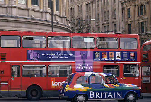 """London, England, UK. Red London bus and black cab with the word """"Britain"""" on it. London buildings visible behind."""