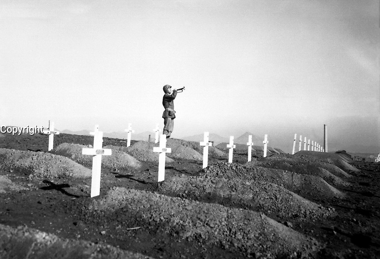 """Cpl. Charles Price sounds """"Taps"""" over the graves of fallen Leathernecks during memorial services at the First Marine Division cemetery at Hungnam, following the division's heroic break-out from Chosin Reservoir.  December 13, 1950.  Cpl. W. T. Wolfe. (Marine Corps)<br /> NARA FILE #:  127-N-A5421<br /> WAR & CONFLICT BOOK #:  1513"""