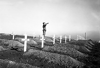 "Cpl. Charles Price sounds ""Taps"" over the graves of fallen Leathernecks during memorial services at the First Marine Division cemetery at Hungnam, following the division's heroic break-out from Chosin Reservoir.  December 13, 1950.  Cpl. W. T. Wolfe. (Marine Corps)<br /> NARA FILE #:  127-N-A5421<br /> WAR & CONFLICT BOOK #:  1513"