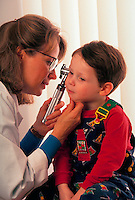 Female doctor examines little boy's ears.