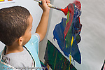 Education preschoool children ages 3-5 art activity boy painting with brush at easel horizontal