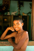 Itaparica Island, Brazil. Smiling boy beside an open window. Bahia State.