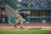 A field crew member repairs the batter's box as the rain begins to fall during a Midwest League game between the Kane County Cougars and Fort Wayne TinCaps at Parkview Field on May 1, 2019 in Fort Wayne, Indiana. Fort Wayne defeated Kane County 10-4. (Zachary Lucy/Four Seam Images)