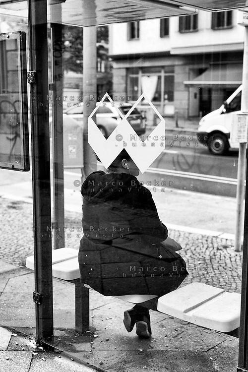 Berlino, quartiere Kreuzberg. Una donna con le cuffiette seduta alla pensilina (del marchio Wall AG) di una fermata dell'autobus --- Berlin, Kreuzberg district. A woman with earphones sitting at the bus stop shelter (of the brand Wall AG)