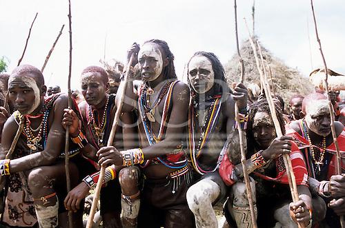 Lolgorian, Kenya. Siria Maasai; Eunoto ceremony; line of kneeling moran with white ochre body paint.