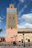 Marrakesh, Morocco. Couple Riding Motorbike Past the Minaret of Moulay El Yazid Mosque.