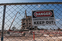 A Danger - Keep Out sign hangs on a chain link fence in the foreground while crews work at demolishing the old Eden Hospital in Castro, Valley, California.