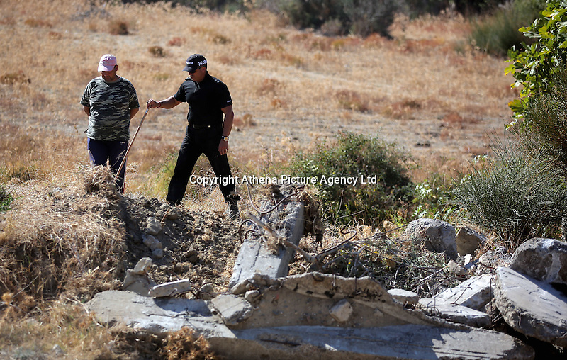 Pictured: A police officer and a workers involved with clearing the new site of the search, where rubble was deposited from the farmhouse where Ben Needham disappeared from in Kos, Greece. Thursday 06 October 2016<br />