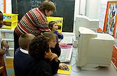MR / Schenectady, NY.Yates Arts in Education Magnet School, Grade 2.Arts-Themed Urban Elementary School.Students use computers at free time. Teacher helps boy (7)..MR: Car19 Pom3.© Ellen B. Senisi