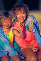 A smiling blond mother and daughter clothed in pastel beachwear sit in the late afternoon sun flashing the peace sign.