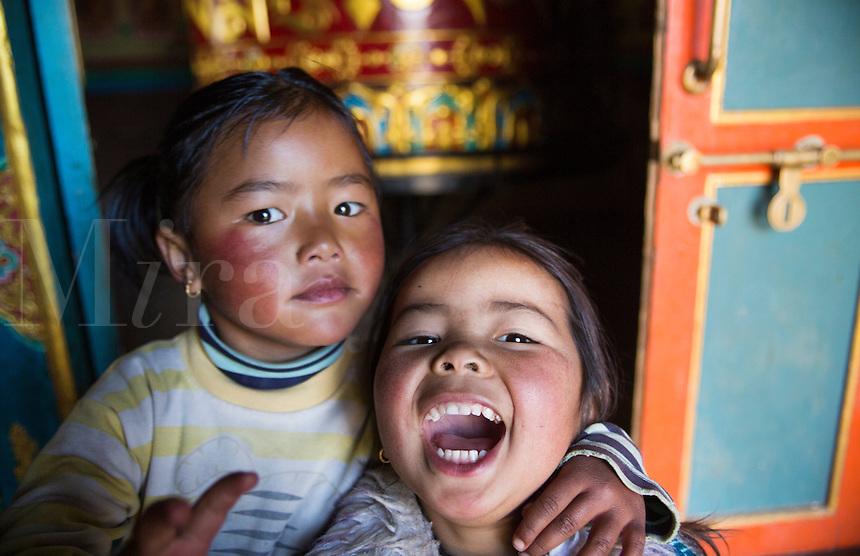 Lukla Nepal Young children pose in front of shrine and prayer wheel in Lukla Solukhumbu  56