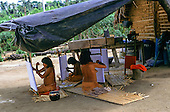 Ipixuna village, Amazon, Brazil. Young Arawete woman weaving cotton cloth for their wedding skirts.