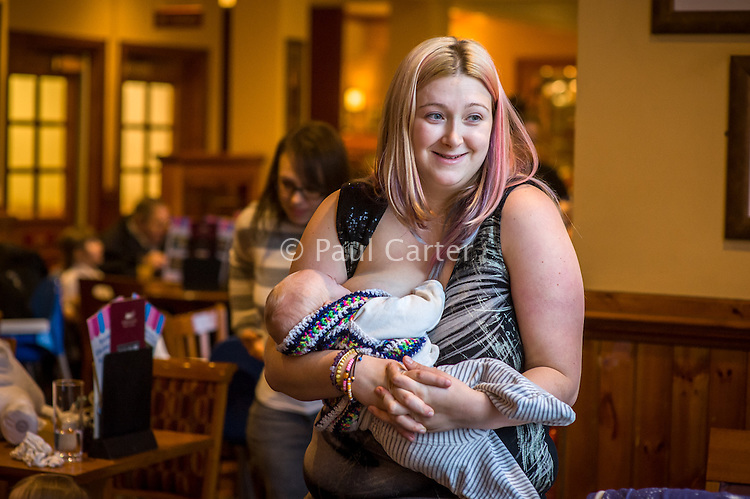 A mother standing and breastfeeding her 12 week old baby in the family restaurant and play area in a pub.