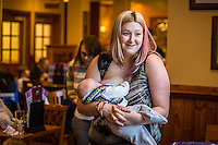 A mother standing and breastfeeding her 12 week old baby in the family restaurant and play area in a pub.<br /> Lancashire, England, UK<br /> <br /> Date Taken:<br /> 07-01-2015<br /> <br /> © Paul Carter / wdiip.co.uk