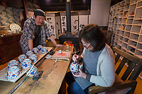 Japan, Ishikawa, Yamanaka. Husband and wife in their studio where they make kutani porcelain, a traditional style of pottery with overglaze. He throws the pots while she paints them with the glaze. Model released