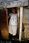 Rio de Janeiro, Brazil. Favela Dona Marta shanty town; woman in candy stripe clothes peering out of a rough wooden shack.
