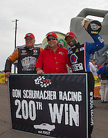 Mar. 17, 2013; Gainesville, FL, USA; NHRA team owner Don Schumacher (center) celebrates with top fuel dragster driver Antron Brown (right) and funny car driver Johnny Gray after winning the Gatornationals at Auto-Plus Raceway at Gainesville. Mandatory Credit: Mark J. Rebilas-