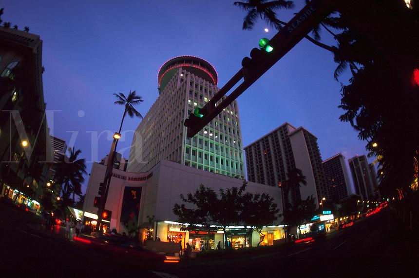 Street scene shot at dusk showing the shops at Waikiki. Honolulu, Hawaii.