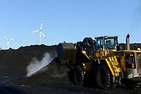Germany, Hamburg, Hansaport import of coal and ore for steel plants and coal power stations, storage place in contrast with wind turbine of Hamburg Energie in harbour / DEUTSCHLAND, Hamburg, Hansaport, Import von Kohle und Erz, Lagerung und Weitertransport zu Kraftwerken und Stahlwerken