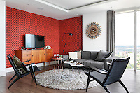 A spacious modern sitting room with a feature wall with red and black patterned covering and a wood floor. The room is furnished with retro style seating around a coffee table and a television set on a wood sideboard.