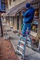 Workers install new awning over sidewalk businesses in Uptown Westerville.
