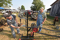 THE FIRST CORDLESS DRILL<br />Eric Montgomery (left) and his dad, Steve Montgomery of Nowata, Okla. work Saturday Sept. 11 2021 an antique drill press powered by an antique engine — what they call the world's first cordless drill — at the fall Tired Iron of the Ozarks tractor and antique show near Gentry. The free show features an array of tractors, farm machinery, antique engines, tools and blacksmithing demonstrations. The show continues today and the public is welcome. The show grounds are at 13344 Taylor Orchard Road near Gentry. From an intersection just west of Gentry city park, signs point the way to the show. Tired Iron of the Ozarks hosts a show in April and September. Look for more photos on Thursday in the Our Town section. Go to nwaonline.com/210921Daily/ to see more photos.<br />(NWA Democrat-Gazette/Flip Putthoff)
