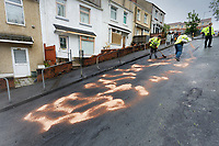 """Pictured: Council workers clean up in Waun-Wen Road in the Mayhill area of Swansea, Wales, UK. Friday 21 May 2021<br /> Re: Gangs of """"yobs"""" have been setting fire to cars and rolling them down a hill in Swansea, Wales, UK.<br /> South Wales Police said they attended """"large scale disorder"""" in the Mayhill area of the city on Thursday evening."""
