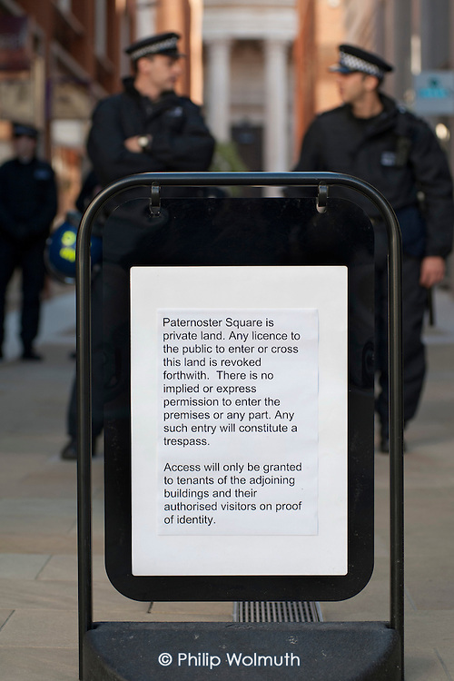 Police guard the Stock Exchange and one of the entrances to Paternoster Square, adjacent to St.Paul's Cathedral, to prevent occupation by Occupy protesters on a global day of action against corporate greed. The square is now owned by the Mitsubishi Estate Company,and is no longer a public right of way.