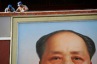 Workers sand the railing above the Mao portrait for repairs in Tiananmen Square in Beijing, China..06 Sep 2006.