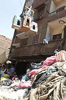 2011 Mokattam Garbage City (alla periferia del Cairo) il quartiere copto dove si vive in mezzo alla spazzatura raccolta: gente in strada accanto ad una montagna di rifiuti. In alto appeso ai balconi delle case un festone con simboli cristiani.