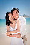 Asian bride and groom embrace while they stroll on Lanikai beach as they look forward to their life as a married couple following their wedding.