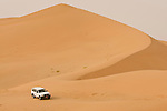 A jeep drives over sand dunes in the Empty Quarter, Ar Rub Al Khali, Oman.