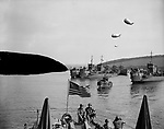 In this photo provided by the U.S. Army Signal Corps., these landing craft, loaded with American troops and guarded overhead by barrage balloons, ride the calm waters of the English Channel, waiting opening of assault on fortress Europe along the French northern coast, June 6, 1944. An American flag flies from the stern of one craft in the foreground. (AP Photo/U.S. Army Signal Corps)