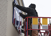 """Sign installers Nate Frihart (foreground) and Austin Yates install a sign, Thursday, February 11, 2021 at the Bentonville Administrative Services building in Bentonville. A crew from Arkansas Sign and Banner installed the big """"B"""" on the City of Bentonville Administrative Services building. Check out nwaonline.com/210212Daily/ for today's photo gallery. <br /> (NWA Democrat-Gazette/Charlie Kaijo)"""