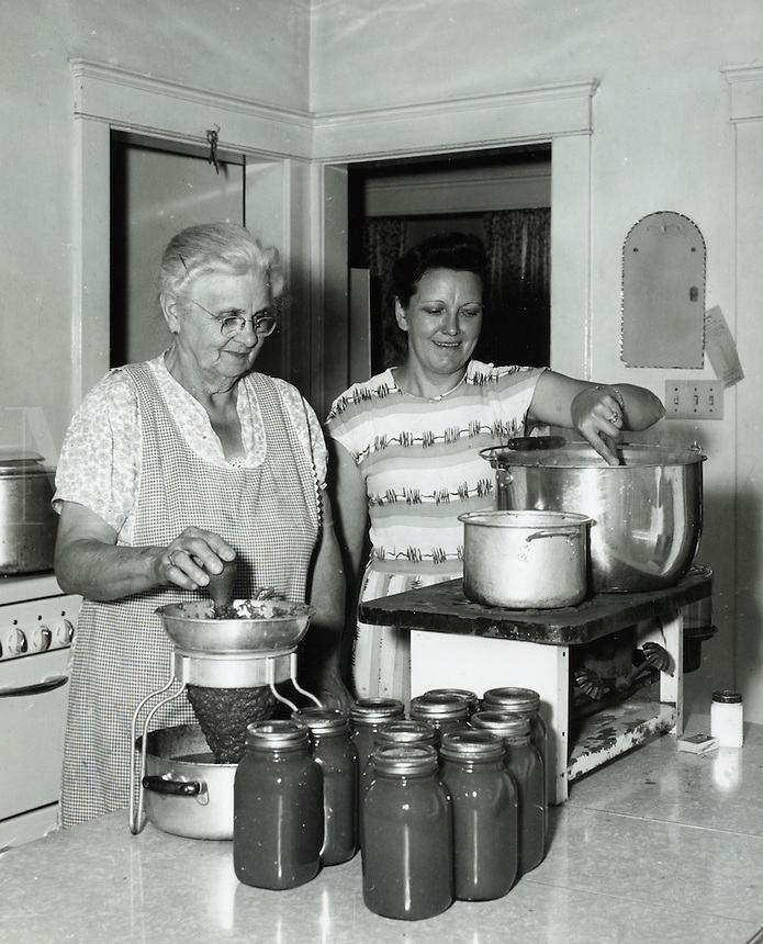 Two women canning vegetables in kitchen. 1950's.