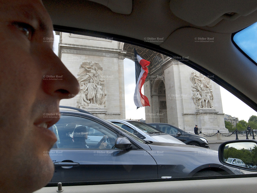 """France. Paris. Arc de Triomphe. Toni Srdanovic drives his car on the Place Charles de Gaulle. Policemen and french flag. The Place Charles de Gaulle, historically known as the Place de l'Étoile, is a large road junction and the meeting point of twelve straight avenues (hence its historic name, which translates as """"Square of the Star""""). It was renamed in 1970 following the death of General and President Charles de Gaulle. It is still often referred to by its original name. Model released. 18.06.10 © 2010  Didier Ruef.."""