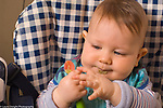 7 month old baby boy in highchair holding spoon, food on face