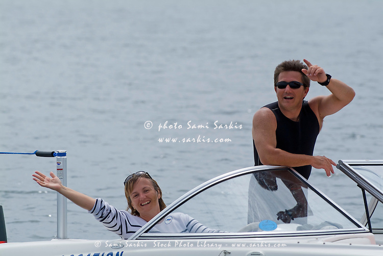 Couple waving from a boat at sea in Biscarrosse, Aquitaine, France.
