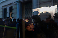 A policeman sits in a bus as protesters enter Lubyanka Square for an unsanctioned anti-Putin demonstration in Moscow, Russia.  Police arrested a number of protesters and opposition leaders.