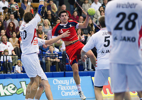 08 JAN 2012 - LONDON, GBR - Great Britain's Sebastian Prieto (#4, in red) leaps and passes during the men's 2013 World Handball Championships qualification match against Austria at the National Sports Centre in Crystal Palace, Great Britain .(PHOTO (C) 2012 NIGEL FARROW)