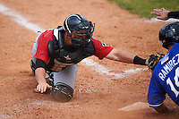 Birmingham Barons catcher Martin Medina (30) attempts to tag Nick Ramirez (14) sliding into home during a game against the Biloxi Shuckers on May 24, 2015 at Joe Davis Stadium in Huntsville, Alabama.  Birmingham defeated Biloxi 6-4 as the Shuckers are playing all games on the road, or neutral sites like their former home in Huntsville, until the teams new stadium is completed.  (Mike Janes/Four Seam Images)