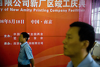 """Amity Printing Company employees watch the inauguration ceremony for the opening of the Amity Printing Company's new printing facility in Nanjing, China....On May 18, 2008, the Amity Printing Company in Nanjing, Jiangsu Province, China, inaugurated its new printing facility in southern Nanjing.  The facility doubles the printing capacity of the company, now up to 12 million Bibles produced in a year, making Amity Printing Company the largest producer of Bibles in the world.  The company, in cooperation with the international organization the United Bible Societies, produces Bibles for both domestic Chinese use and international distribution.  The company's Bibles are printed in Chinese and many other languages.  Within China, the Bibles are distributed both to registered and unregistered Christians who worship in illegal """"house churches."""""""