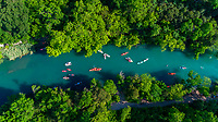 This is an aerial view from a drone high above the emerald green waters of Barton Creek, a lazy half mile run down to the Colorado River where many paddlers go for a leisurely few hours on the water in canoes and kayaks. Recent residential development on the upper reaches of the creek have eliminated some previous access points, and others are either difficult to find, difficult to access, or both. Starting barely northeast of the Hays-Travis County in the Texas Hill Country, most of the creek flows inside Austin city limit, ending at downtown Austin where it meets the Colorado River at Town Lake alongside Zilker Park.