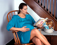 Pregnant woman reading in a chair.